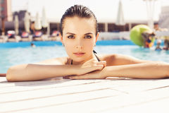 Beautiful brunette woman on the beach in pool alone relaxing in Stock Photos