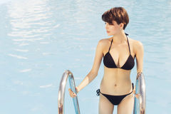 Beautiful brunette woman on the beach in pool alone relaxing in Stock Images