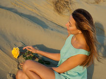 Beautiful brunette woman on the beach with a yellow rose Stock Image