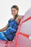Beautiful brunette woman on bench Stock Photo