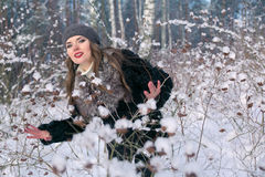 Beautiful brunette woman in a beret and fur coat posing and smiling on the background of snowy forest Royalty Free Stock Photo