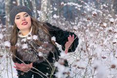 Beautiful brunette woman in a beret and fur coat posing and smiling on the background of snowy forest Royalty Free Stock Image