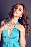 Beautiful brunette woman with bijou, wears elegant dress Royalty Free Stock Images