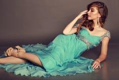 Beautiful brunette woman with bijou, wears luxurious dress royalty free stock photography