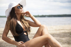 Beautiful brunette woman in black dress bikini Stock Photo