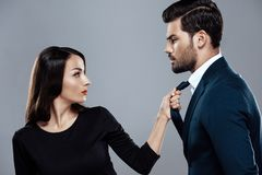 Beautiful brunette woman in black dress is holding a stylish man by tie. royalty free stock photo
