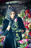 Beautiful brunette woman in black at florist shop Stock Photo