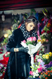 Beautiful brunette woman in black at florist shop Royalty Free Stock Image