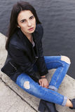 Beautiful brunette woman in black leather jacket sitting on the Stock Images