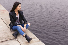 Beautiful brunette woman in black leather jacket sitting on the Stock Photo