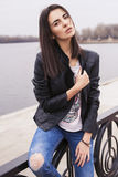 Beautiful brunette woman in black leather jacket sitting on the Royalty Free Stock Photo