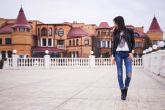 Beautiful brunette woman in black leather jacket walking on the Royalty Free Stock Images