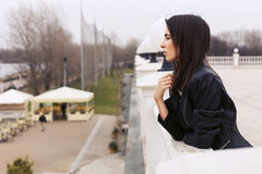 Beautiful brunette woman in black leather jacket walking on the Stock Photography