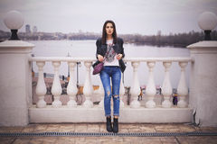 Beautiful brunette woman in black leather jacket walking on the Stock Photos