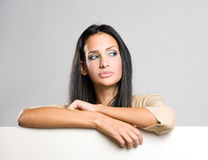 Beautiful brunette woman with blank sheet. Stock Photos