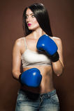 Beautiful brunette woman with blue boxing gloves. On brown background Stock Photo