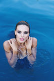 Beautiful brunette woman in a blue swimsuit inr the pool. Portrait of a beautiful woman with long hair. Stock Photos