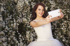 Beautiful brunette woman bride in a garden park in white wedding. Dress, curly hairstyle and a smile make selfie on a mobile phone. warm weather, outdoors. copy Stock Photos