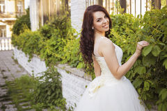 Beautiful brunette woman bride in a garden park in white wedding Stock Photo