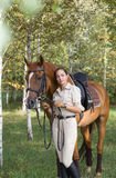 Beautiful brunette woman with a brown horse Royalty Free Stock Image