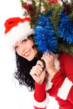 Beautiful brunette woman carrying a Christmas tree. Beautiful smiling brunette woman carrying a Christmas tree on her back isolated against white background Royalty Free Stock Photos