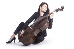 Beautiful brunette woman with cello sits on floor of studio agai Royalty Free Stock Photo