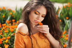 Beautiful brunette woman with colored makeup smelling flower, over marigold flowers field royalty free stock photography