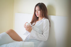 Beautiful brunette woman drinking and morning coffee in bedroom Royalty Free Stock Photography