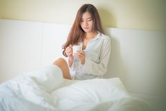 Beautiful brunette woman drinking and morning coffee in bedroom Stock Photos