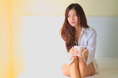 Beautiful brunette woman drinking and morning coffee in bedroom Royalty Free Stock Images