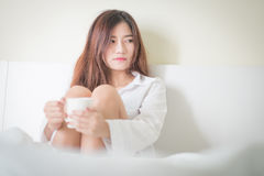Beautiful brunette woman drinking and morning coffee in bedroom Stock Image