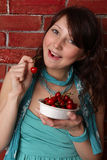 Beautiful brunette woman eating berry Royalty Free Stock Photography