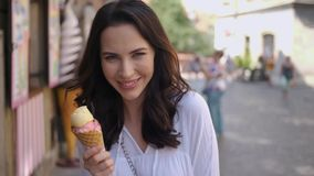 Beautiful brunette woman eating delicious and sweet ice cream. She walks on city street in urban summer outdoor stock video footage