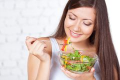 Beautiful brunette woman eating salad Stock Photo