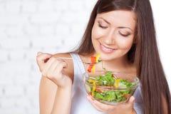 Beautiful brunette woman eating salad Stock Photo