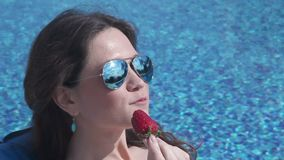 Beautiful brunette woman eating sweet strawberry, happy face