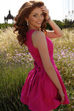 Beautiful brunette woman in elegant dress posing in lavender field Royalty Free Stock Photo