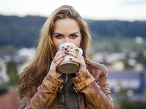 Beautiful brunette woman enjoying coffee outside royalty free stock photography