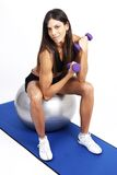 Beautiful brunette woman exercising. On a blue mat with purple dum bells royalty free stock photo