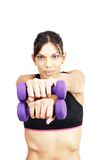 Beautiful brunette woman exercising. With purple dum bells. Focus is on the dum bells royalty free stock photo