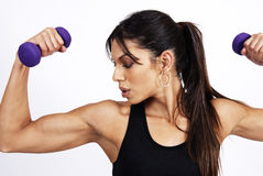 Beautiful brunette woman exercising. With purple dumbbells Stock Images