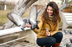 Beautiful brunette woman  feeding pigeons Stock Photo