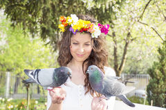 Beautiful brunette woman  feeding pigeons Royalty Free Stock Photo