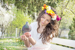 Beautiful brunette woman  feeding pigeons Stock Images
