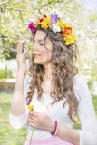 Beautiful brunette woman with flower wreath in the spring garden Stock Photos