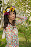 Beautiful brunette woman with flower wreath in the spring garden Royalty Free Stock Photography