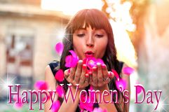 Beautiful brunette woman with flowers blowing petals from her hands. Happy International Women`s Day text with blurred background. Outdoor shoot Royalty Free Stock Image