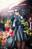 Beautiful brunette woman with gloves choosing flowers at the florist shop. Fashionable female with sunglasses and head scarf Stock Photo