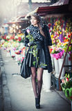 Beautiful brunette woman with gloves holding a rose in front of  florist shops.   Royalty Free Stock Photography