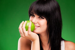 Beautiful brunette woman with green apple on green background Stock Photography
